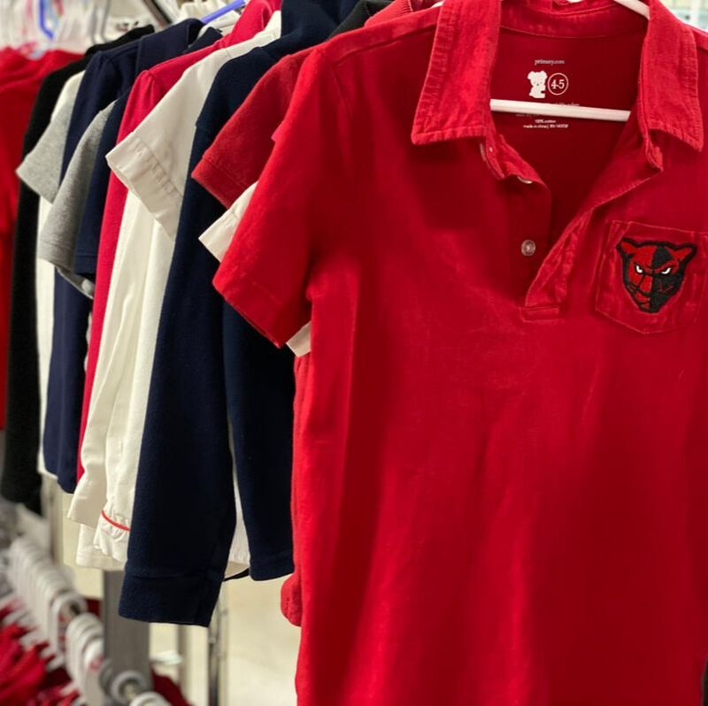 Red, Navy blue, White, and Gray uniform polos are hanging on clothing racks. There is emphasis on a red polo shirt that contains a Petal panther logo.